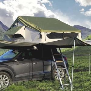 Coche gris con tienda de techo montañas verdes