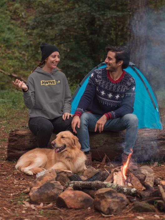 2 personas sentadas de camping con un perro