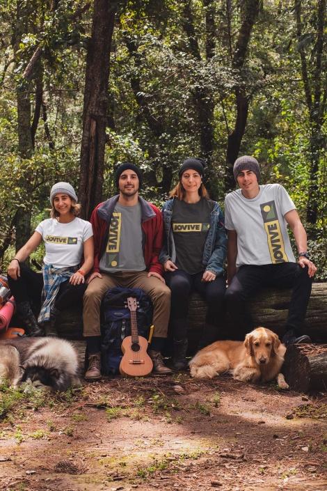4 jovenes con camisetas Jovive en camping y un perro