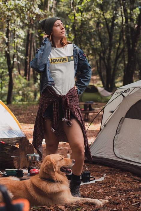 Mujer de camping con perro en el bosque
