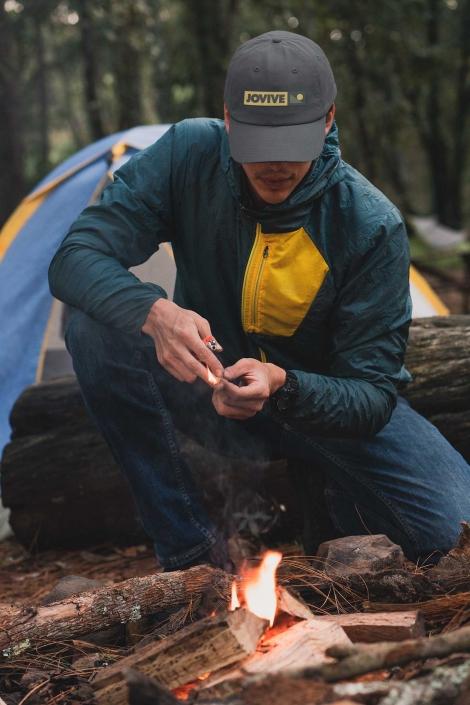 Hombre con gorra agachado haciendo fuego