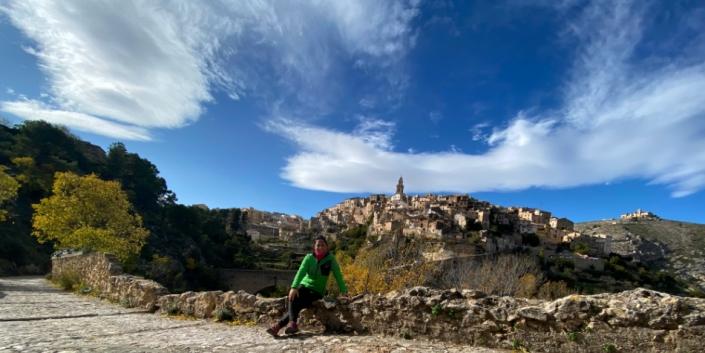 Mujer sentada muro de piedra en Bocairent