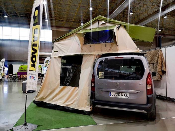 Furgoneta con tienda para techo Jovive Tent desplegada en feria para caravanas