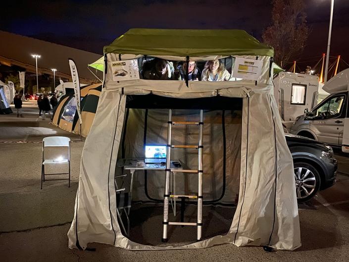 Tres personas en tumbadas dentro de una tienda Jovive Tent, vistos desde fuera