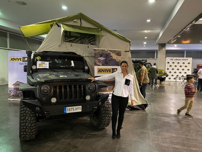 Mujer posa junto todo terreno que monta la tienda Jovive Tent