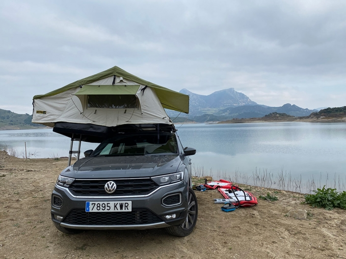 Vehiculo camperizado con tienda de techo junto a un lago