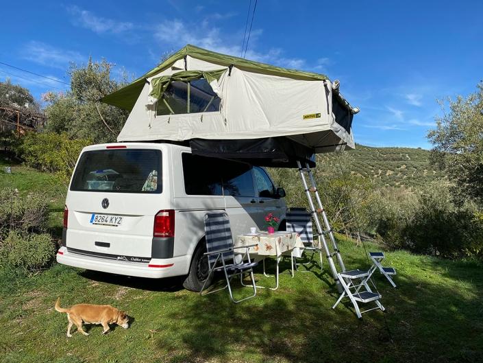 Furgoneta blanca con tienda de techo en camping