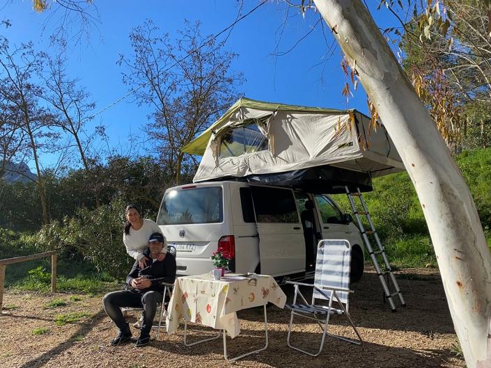 Vehículo camperizado con tienda de techo en el bosque